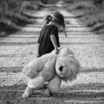Mädchen mit Teddybär auf einem Weg schwarzweiß