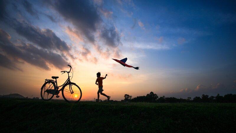 Kind das im Sonnenuntergang über ein Feld rennt