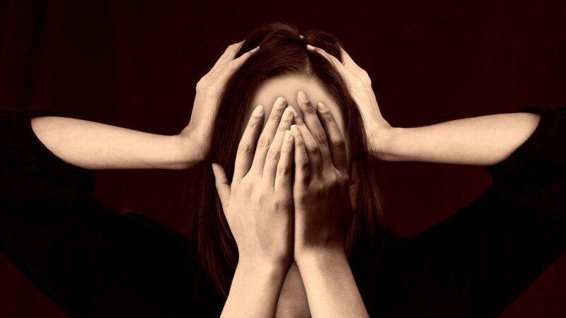 Frau die sich die Hände vors Gesicht hält