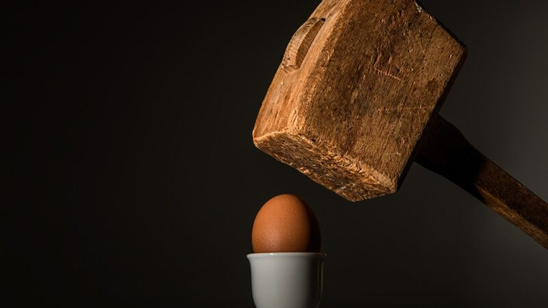 Hammer der auf Ei schlägt